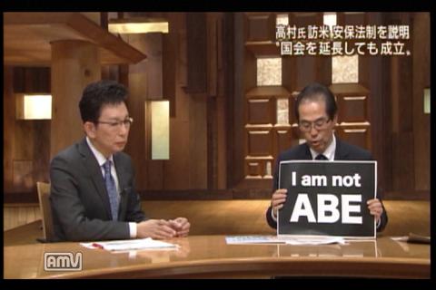 「I am not ABE」と書いた手製の紙を掲げる