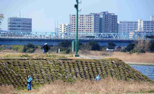 川崎市川崎区の現場周辺の堤防や土手を入念に調べる捜査員ら