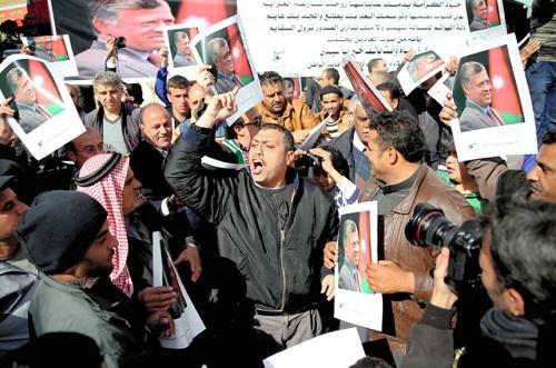ヨルダン国王の写真を掲げ、拘束中のヨルダン軍パイロットのムアーズ・カサースベ中尉の救出を訴える人々=30日正午、アンマン、三浦英之撮影