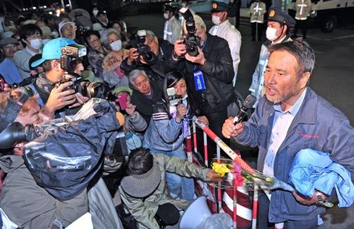 釈放され、支援者の前で礼を述べる沖縄平和運動センターの山城博治議長(右)=23日午後7時46分、名護市東江の名護署前