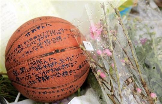 上村遼太君が遺体で見つかった多摩川河川敷に供えられた、メッセージの書かれたバスケットボール=24日午前、川崎市川崎区(メッセージを書いた人の名前をモザイク加工しています)