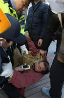 米大使襲撃事件で警備員らに取り押さえられたキム・ギジョン容疑者=5日、ソウル(ロイタ-)